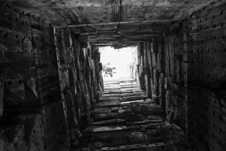 Deep well, the walls of which are lined with stone. Bottom view. Light at the end of the tunnel. Light at the end of the road. Background.