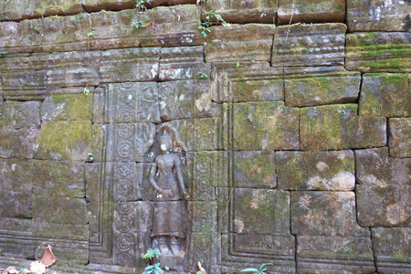 Antique stonework decorated with bas-relief. Stone carving. Ancient ruins overgrown with moss.