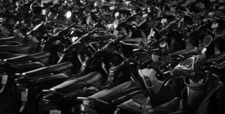 scooters parked in dense rows, beautiful night lighting, soft focus, background