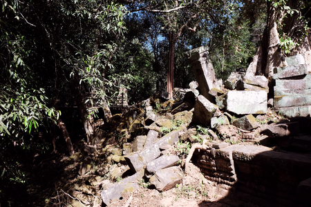 The stone blocks of the ancient ruins are lit by the bright midday sun. Ruins in the jungle of Indochina.