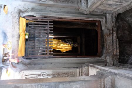Buddha statue dressed in gold clothes. A small Buddhist sanctuary in the temple of Angkor.