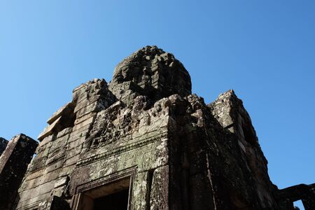 Corner of a medieval stone tower. Fragment of the ancient Khmer temple of Bayon.