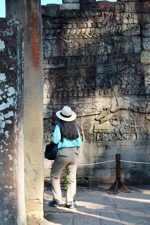 Black-haired woman in a white hat examines an ancient bas-relief. Woman with gray hair in her hair. Tourist among the medieval ruins.