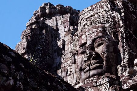 A huge human face built of stone blocks. Huge human faces on the towers of the Bayon temple in Cambodia. Architectural art of ancient civilizations.