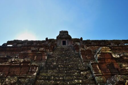 Staircase of the ancient Hindu temple leading up. The ruins of a medieval Khmer temple. Dilapidated stone structure.