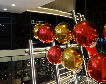 Huge red and yellow decorative balls hang near the shopping center. Christmas holiday decorations.