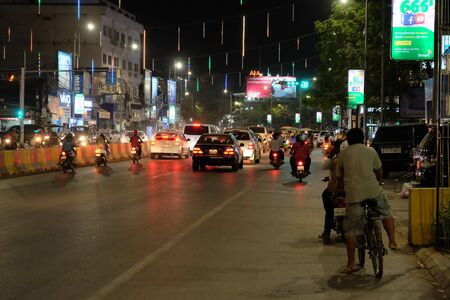 Siem Reap, Cambodia, December 23, 2018 Vehicles are waiting at the traffic light. Cyclist at night on the roadway. Night traffic of the Asian city.