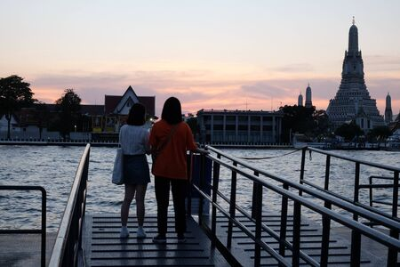 Bangkok, Thailand, December 25, 2018 two young girls stand on the river bank and admire the temple of Wat Arun at sunset. Berth for a river ferry.
