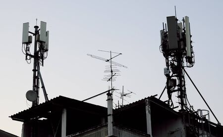 A large number of antennas are located on the roof of the house.