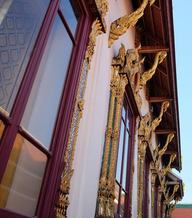 Gilded decorative elements adorn the wall of a Buddhist temple. Stok Fotoğraf
