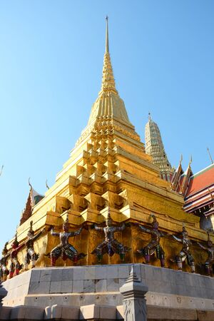 Gilded conical tower on the territory of a Buddhist temple in Bangkok.