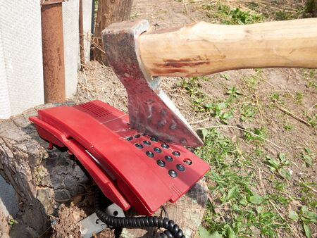 A large ax sticks out in an outdated push-button telephone.