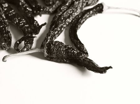 A lot of peppers on a white background. Black and white photo.