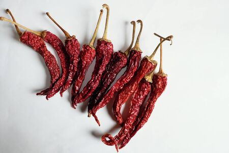A lot of red peppers on a white background.