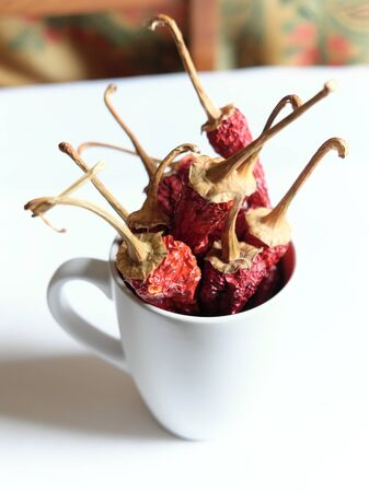 A lot of peppers in a cup on a white background.