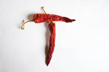 Letter T lined with red peppers on a white background. Symbol in the form of the letter T. Pepper lined in the letter T on a white background.