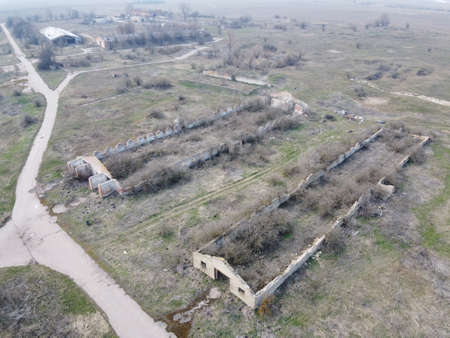 Destroyed agricultural buildings, aerial view. Abandoned livestock farm.
