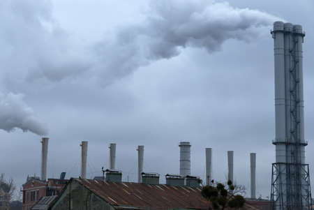 Smoke comes from industrial chimneys above the rooftops. The sky is covered with gray clouds. Environmental pollution.