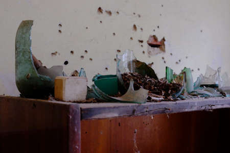Shards of broken glassware. Fragments of cans and bottles, which were used as a target for shooting. Bullet holes in the wall. The consequences of shooting bottles.