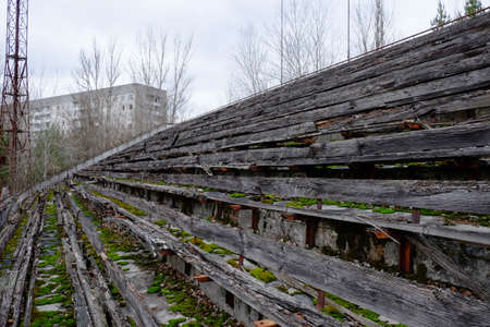 The stands of an abandoned stadium in Pripyat. Old wooden benches in the stadium.