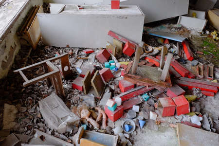 Scattered furniture and toys in an abandoned kindergarten in Pripyat. Mess and rubbish in the room. An abandoned building in the Chernobyl resettlement zone.