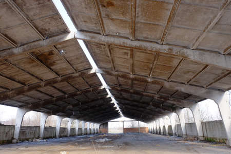 A dilapidated concrete industrial structure. Storage with concrete roof.