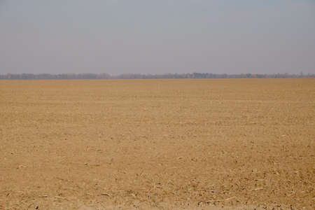 Cloudy gray sky over a plowed agricultural field. Clay soil. Landscape.