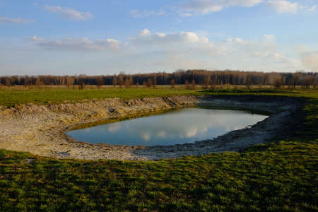 A small drying pond in the evening in the field. Cloudy sky over the lake. Landscape.