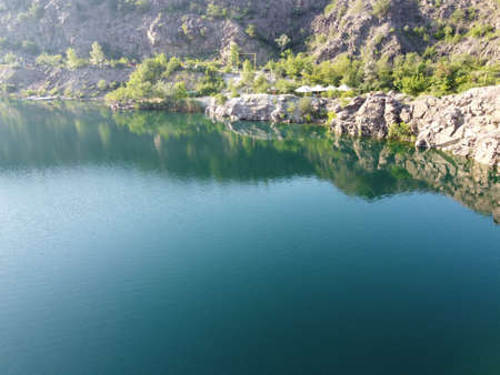 Rocky shore of the Radon Lake on a sunny summer morning. Aerial view of an old flooded granite quarry. A picturesque pond.