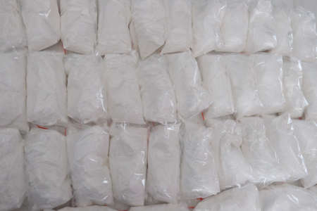 A large number of transparent sachets filled with white powder. White powder packaged in small sachets.