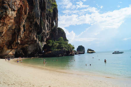 People enjoying the blue sky and turquoise beach in Krabi, Thailand