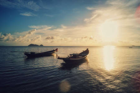 A beautiful sunset at the beach of Koh Phangan with boats and a bright sun, in Thailand