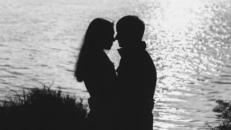 pár v lásce objímání u vody, silueta