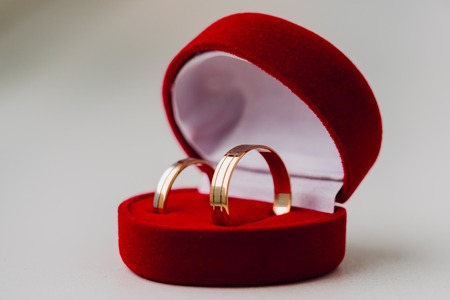 Golden wedding rings in red box on white background