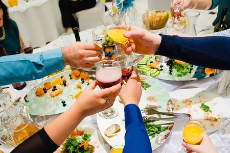 clink: many hands with different glasses of wine clink and jingle in the holiday