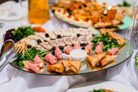 sliced meats from ready meats in the restaurant, with olives and parsley Stock Photo