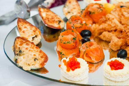 red cooked: pieces of red cooked salmon and mussels are beautiful on a plate for a holiday dinner Stock Photo