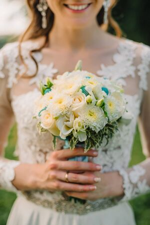happy wedding: wedding white bouquet of roses in the hands of a happy bride in elegant white wedding dress