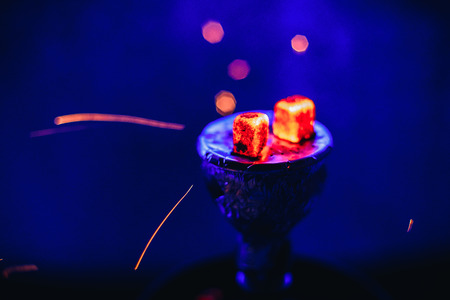 Shisha hookah with glowing red embers and flying sparks in bowl on blue background