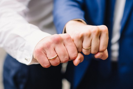 hands of two men with wedding gold rings in the shape of a fist Reklamní fotografie
