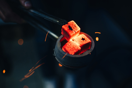 bowl of hookah with red hot coals in hands of hookah Reklamní fotografie
