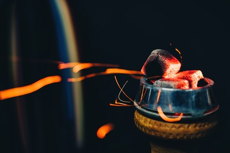 coals on bowl of hookah for tobacco Smoking close up with sparks on dark background