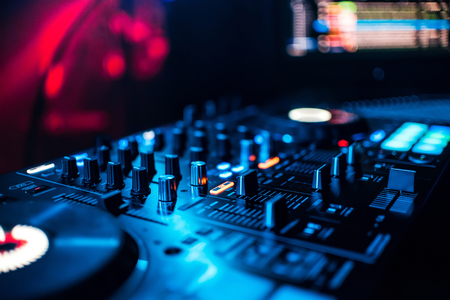 control buttons and mixing music on professional equipment for mixing DJ