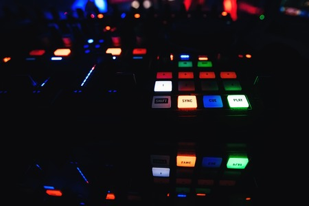 buttons on mixer DJ with lighting for creating and mixing music with a dark