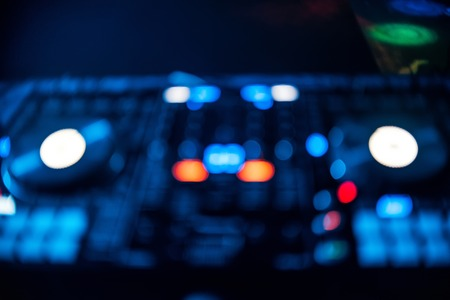 wazig uit focus Board DJ met gloeiende knoppen in nachtclub Stockfoto