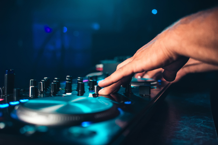 DJ controls and mix music on music mixer in nightclub Stock Photo