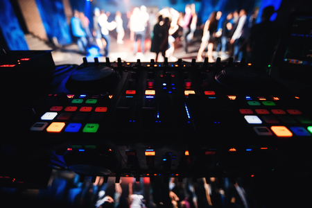 music DJ Desk with blurred background of dance floor with dancing people in night club