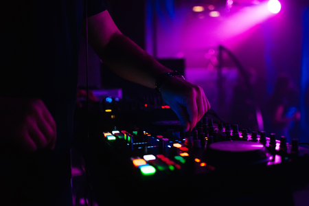 DJ controls the music in nightclub moving the controllers on the music Board Stock Photo