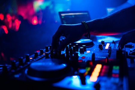 DJ mixing music moving the controllers on mixer in night club