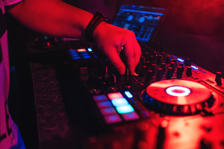 DJ managing regulators and volume of music at party in night club with red glow